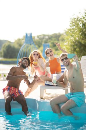 Boyfriends and girlfriends. Boyfriends and girlfriends smiling while taking photo together near pool