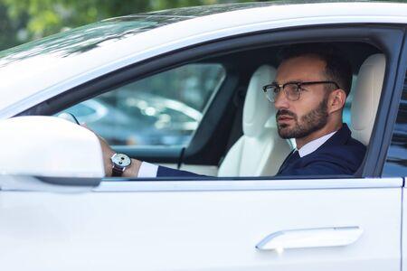 Nello specchietto laterale. Uomo barbuto che indossa un orologio a mano che guarda nello specchietto laterale mentre guida la sua auto