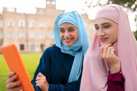 Sitting near friend. Student wearing blue hijab holding orange tablet sitting near friend with laptop