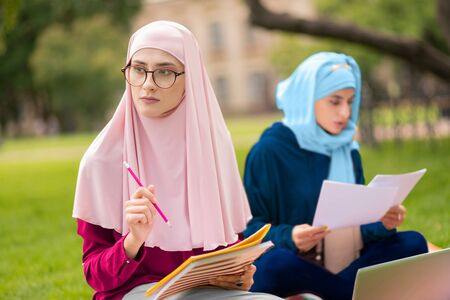 Studying with friend. Muslim student wearing pink hijab and glasses studying with friend