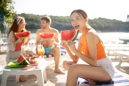 Woman feeling excited. Young beautiful woman feeling excited before trying watermelon