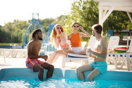 快乐的女朋友。快乐的女朋友在泳池派对上看着他们强壮英俊的男人