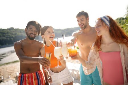 Girlfriend and friends. African-American man standing near girlfriend and friends while drinking cocktails