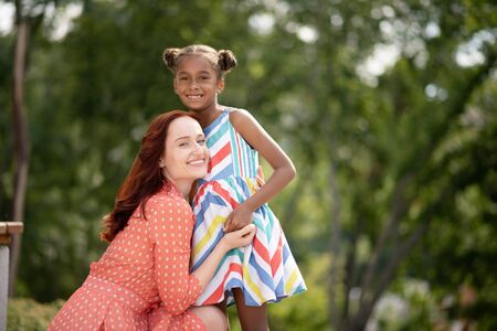 African-American girl. Beaming African-American girl wearing bright dress hugging her caring mother