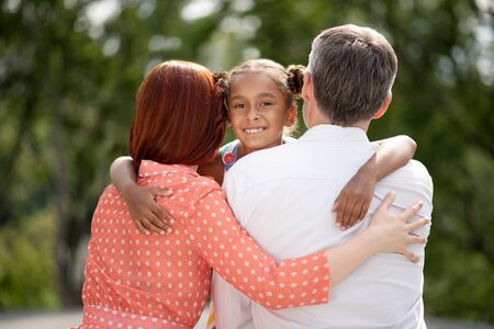 Hugging foster parents. Dark-skinned beaming girl feeling happy while hugging her foster parents