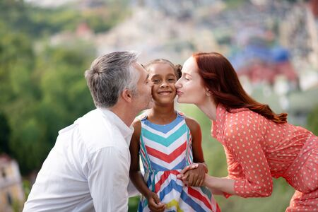 Parents kissing. Adoptive parents kissing their cute dark-skinned girl while walking in the park