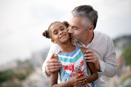 Foster father kissing. Grey-haired loving caring foster father kissing his cute dark-skinned daughter
