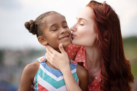 Mother kissing. Red-haired foster mother kissing her lovely dark-skinned girl while walking outside