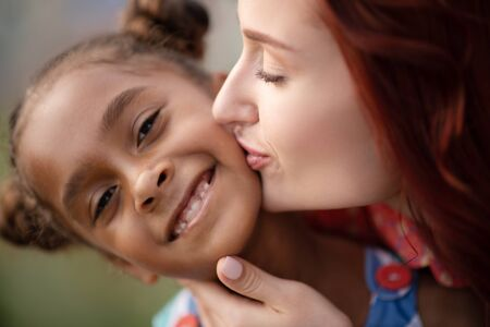 Girl smiling broadly. African-American adopted girl smiling broadly while mother kissing her
