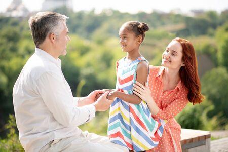 Conociendo al padre adoptivo. Linda chica afroamericana se siente emocionada al conocer a su padre adoptivo