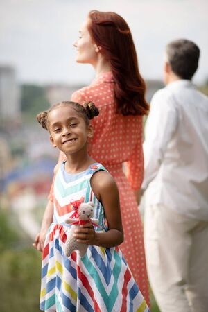 Girl feeling happy. Dark-skinned adopted girl feeling happy walking with parents at the weekend