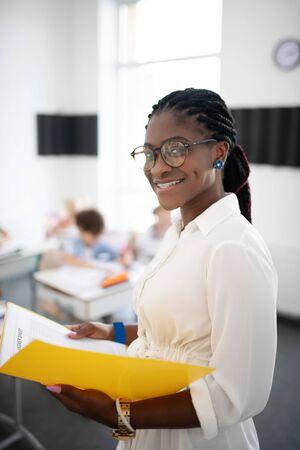 Beaming teacher. Beaming dark-skinned primary school teacher holding notebook while standing in classroom