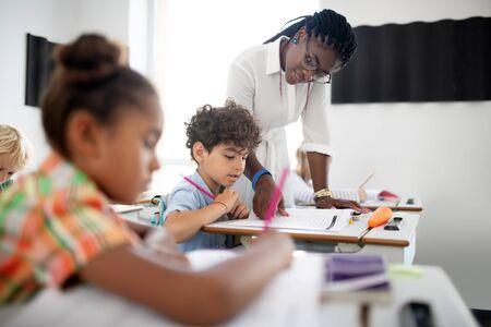 Curly boy listening. Curly dark-haired boy listening to African-American teacher wearing glasses 免版税图像