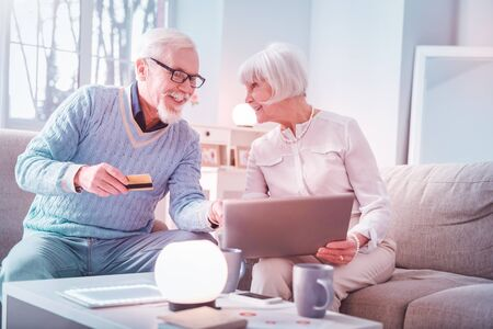 Paying online. Modern elderly man and woman feeling excited while processing payment while paying online