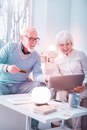 Helpful husband. Helpful elderly bearded husband teaching his wife using internet and buying online