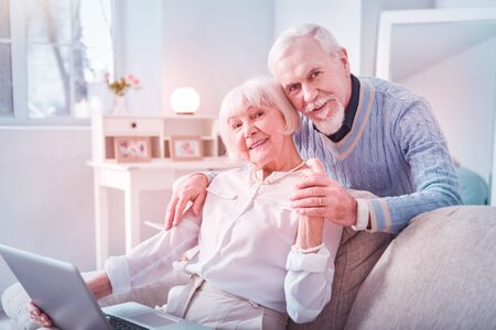 Cute couple. Couple of cute elderly man and woman hugging each other while spending weekend at home Banco de Imagens
