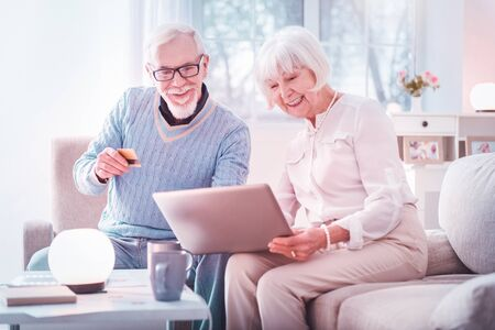 Shopping online. Couple of modern grandparents feeling very excited while shopping online together