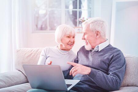 Stylish lady. Stylish elderly lady wearing nice necklace sitting near her bearded husband at home