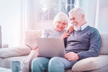Beaming couple. Beaming retired husband and wife laughing out loud watching comedy on laptop