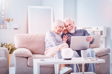 Cute couple. Cute retired couple sitting in living room drinking tea and watching comedy together