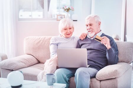 Shopping online. Bearded elderly man holding bank card shopping online with his elegant beautiful wife