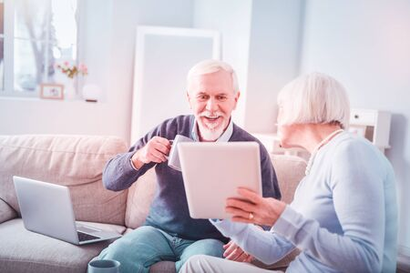 Woman with tablet. Modern retired elegant blonde-haired woman holding her tablet showing husband some photos