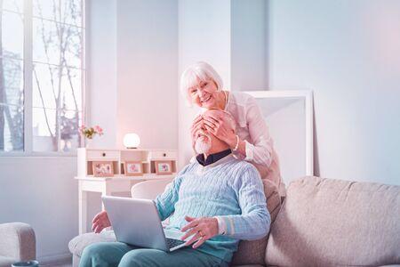 Close eyes. Beautiful beaming elderly lady having fun while closing eyes for her bearded husband Banco de Imagens