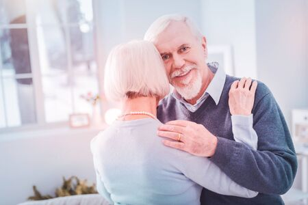 Hugging wife. Bearded grey-haired elderly husband hugging his appealing wife while having romantic date