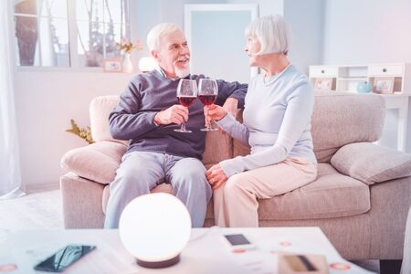 Red wine. Couple of pensioners drinking red wine while having romantic date sitting on beige sofa at home Banco de Imagens