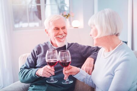Clanging glasses. Couple of beaming pensioners clanging their glasses having romantic dinner celebrating anniversary
