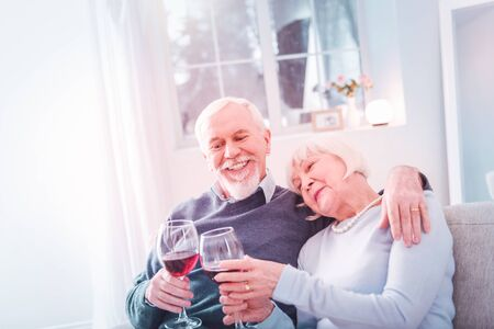 Lean on shoulder. Beautiful elderly lady leaning on shoulder of her loving caring man drinking red wine