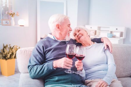 Wine together. Stylish elderly lady wearing necklace looking at husband drinking wine together