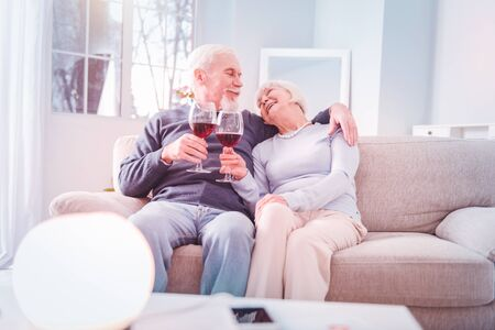 Wine after dinner. Couple of good-looking happy pensioners feeling cheerful while drinking some wine after dinner Banco de Imagens