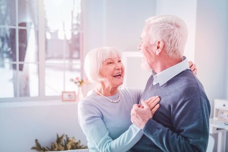 Cheerful couple. Cute loving couple of pensioners feeling truly happy and cheerful dancing at home
