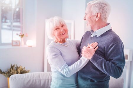 Beaming lady. Beaming elderly lady wearing blue sweater feeling amazing while dancing with her husband