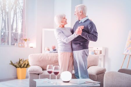 That anniversary. Couple of cute beaming pensioners feeling happy celebrating their anniversary with wine