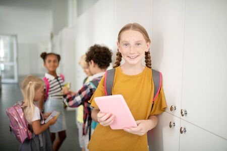 Girl with tablet. Appealing schoolgirl with backpack holding pink tablet while standing near lockers