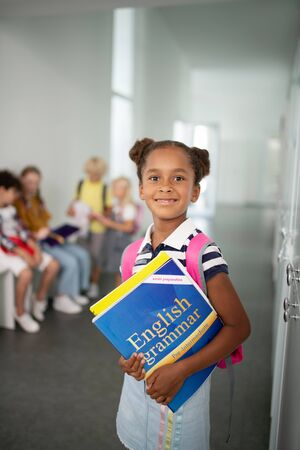Girl with books. Cute dark-skinned girl wearing striped t-shirt holding books while standing at school Stok Fotoğraf