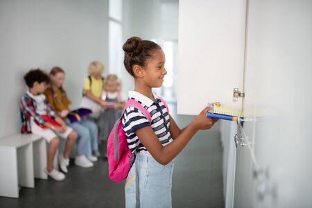 Girl putting books. Smiling dark-skinned girl putting books inside locker while having break Reklamní fotografie
