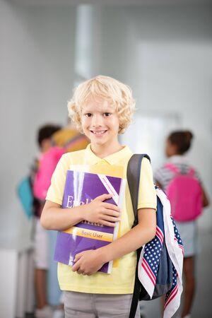 Cheerful schoolboy. Cheerful schoolboy holding books while feeling excited before English lesson