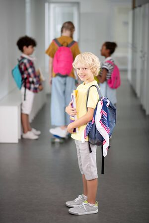 Boy wearing backpack. Cute blonde-haired boy with backpack standing in the school hallway Stok Fotoğraf