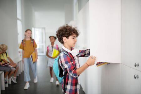 Jongen die locker opent. Krullende donkerharige jongen met een vierkant overhemd dat een locker opent terwijl hij boeken pakt