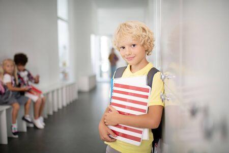Handsome boy. Dark-eyed handsome boy holding notebooks standing near lockers in school corridor Stok Fotoğraf