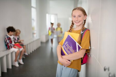 Beautiful schoolgirl. Beautiful schoolgirl holding English grammar boy while standing near locker