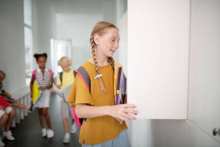 Girl opening locker. Smiling cheerful girl wearing backpack opening her locker at school