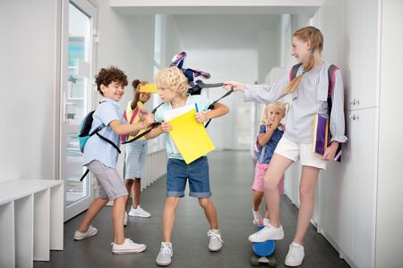 Children pushing. Rude children bullying poor blonde boy while taking his backpack and pushing Stock Photo