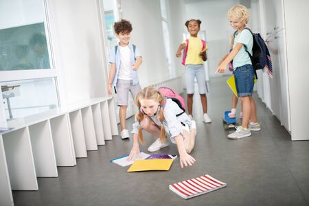 Notebooks on floor. Girl taking her notebooks from floor after children pushed and bullied her