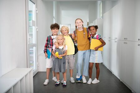 Pupils near lockers. Stylish happy pupils standing near lockers all together before lesson starts Stok Fotoğraf