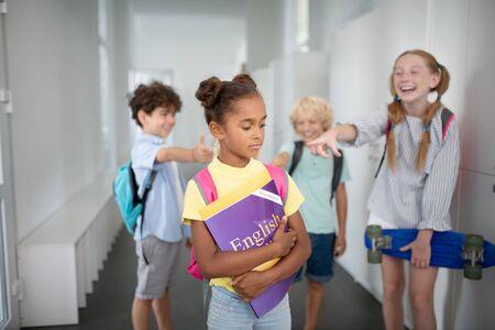 Suffering from bullying. Dark-skinned girl feeling lonely while suffering from bullying at school Stock Photo
