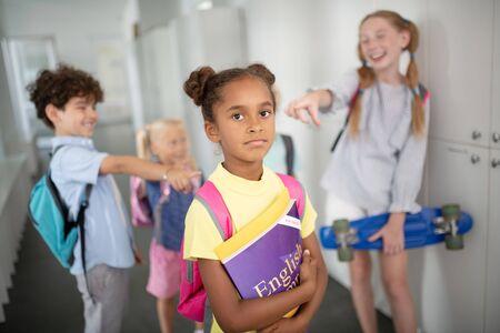 Schoolgirl feeling offended. African-American schoolgirl feeling offended and frustrated at school Stock Photo